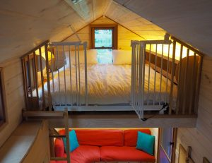 Warm white LED light strips splash light off the ceiling to soften the lighting in the loft bedroom of a tiny house.