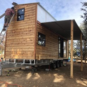 "A tiny house shell to ""Lock Up Plus"" headed to South Australia where the DIY owners will complete their home. A 7.2M tiny house on flat top trailer rated to 4500kg. Includes Fred's Unified Construction Method™ which fundamentally appreciates first and foremost a THOW is a road vehicle which will vibrate, rattle and roll. So we created a construction method that unifies the whole of the house & trailer to stand up to it's life as a vehicle, so you can safely use it as a home. Includes, western red cedar siding, fold down verandah awning that increases liveable space by 95%, deck available, asymmetrical roof designed to accept large solar panels. DIY tiny house shells for sale from Fred's Tiny Houses, Castlemaine, VIC Australia."